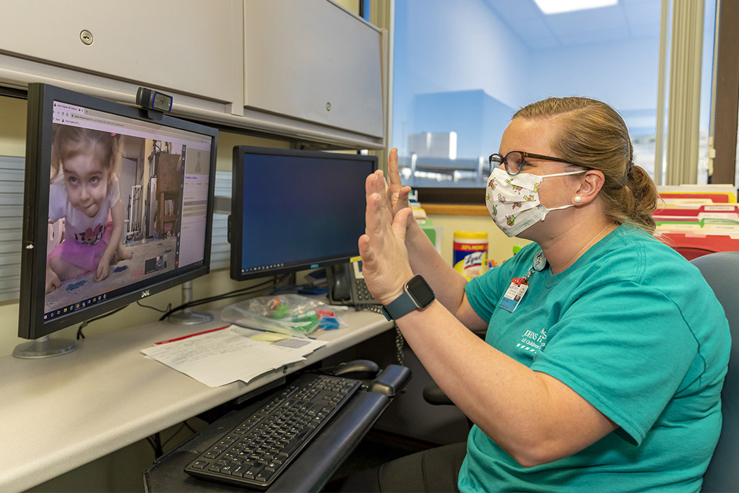 A photo of occupational therapist Breanna Howell working with Lily during a telemedicine appointment.