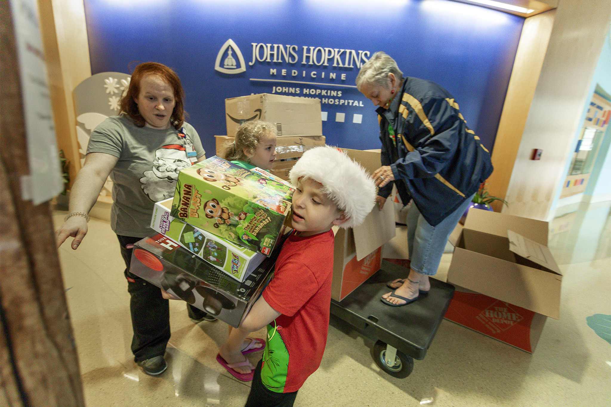 Adyn and Abby unload donations of toys they collected for children at Johns Hopkins All Children's.