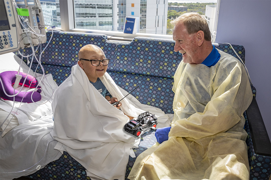 The photo shows Johns Hopkins All Children's volunteer Owen Young visiting with patient Gabriel in early March before social and physical distancing and masking guidelines were announced.