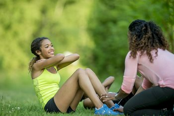 The picture shows a mother and daughter exercising together.