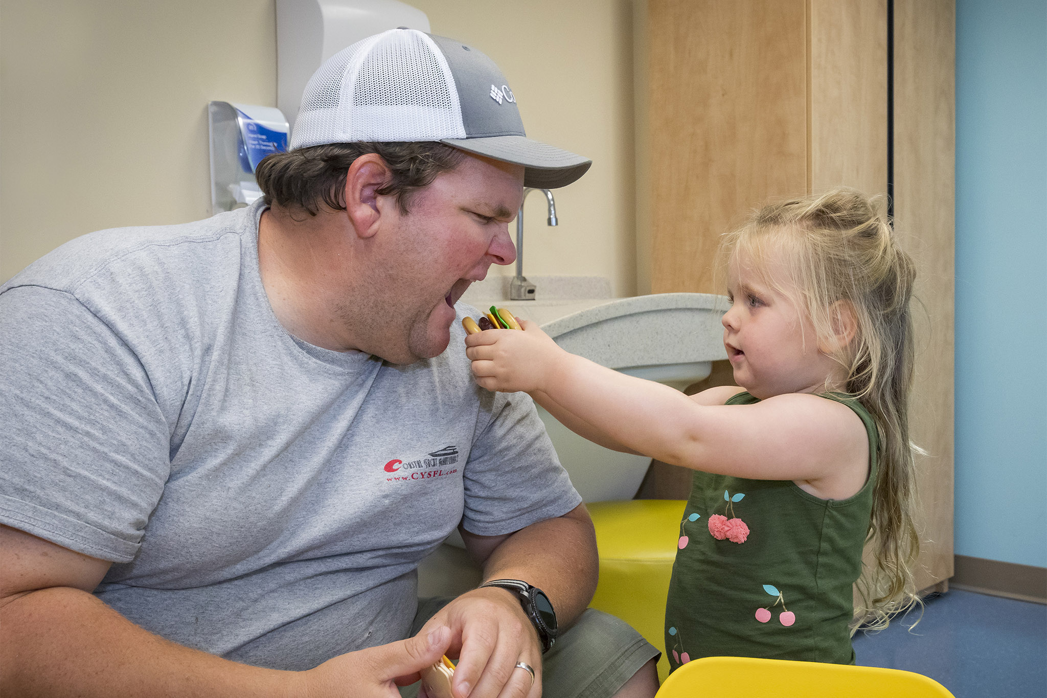 Zoey and her dad Dustin enjoy a meal of pretend hamburgers in RJ's Activity Center at Johns Hopkins All Children's.