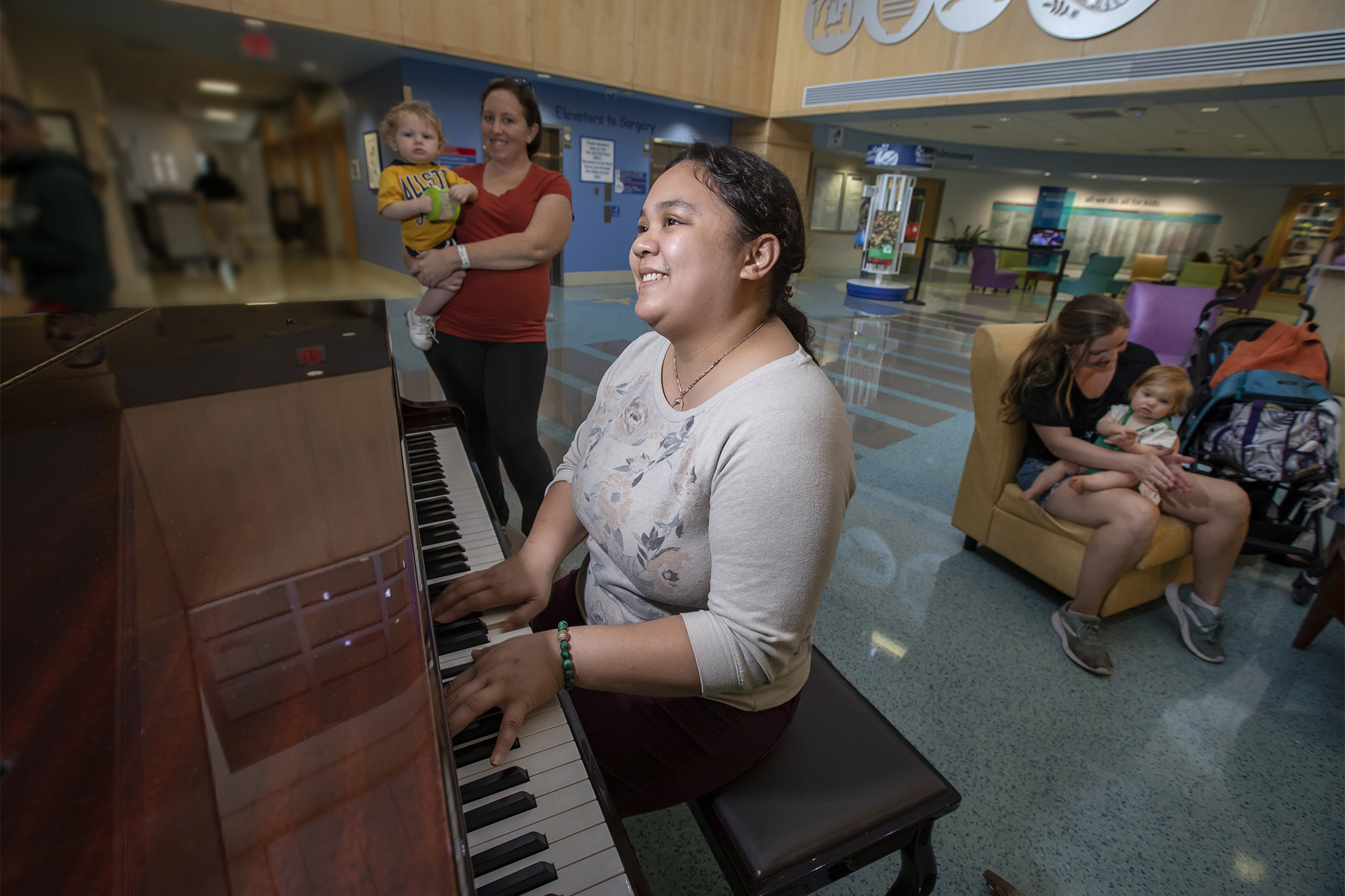 Environmental Services employee Katrina Bernal plays the piano in the hospital lobby