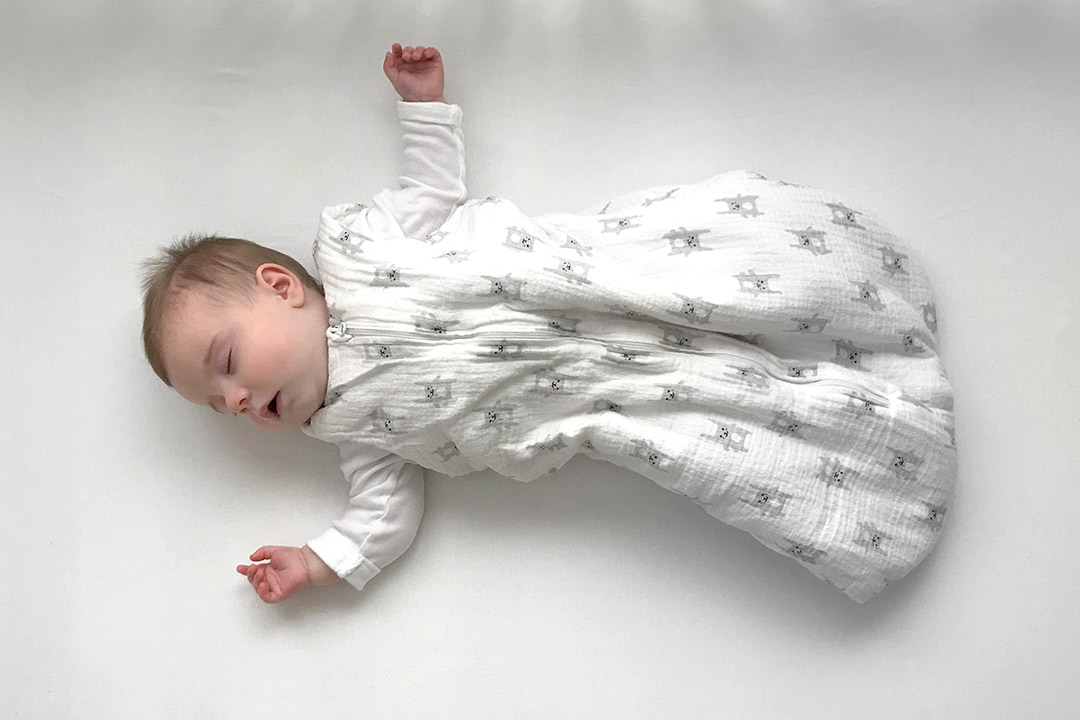 The photo shows a baby in a crib, following safe sleep practices like not having anything in the crib with the baby and the baby sleeping on his or her back.