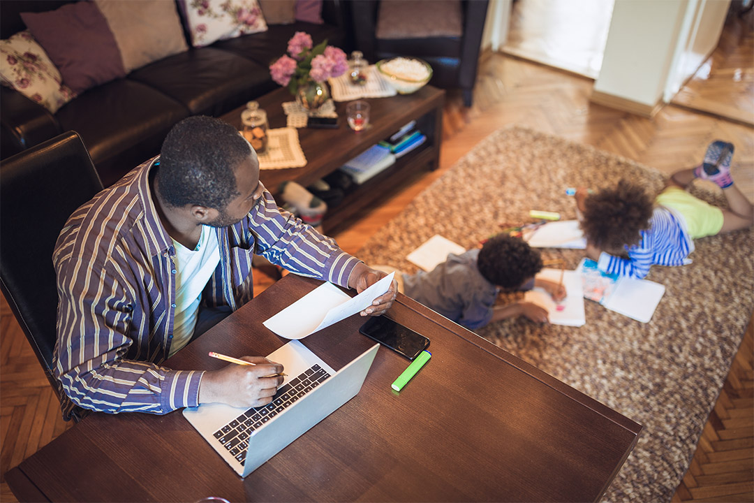 The image shows a parent working from home while the kids are drawing in the living room.